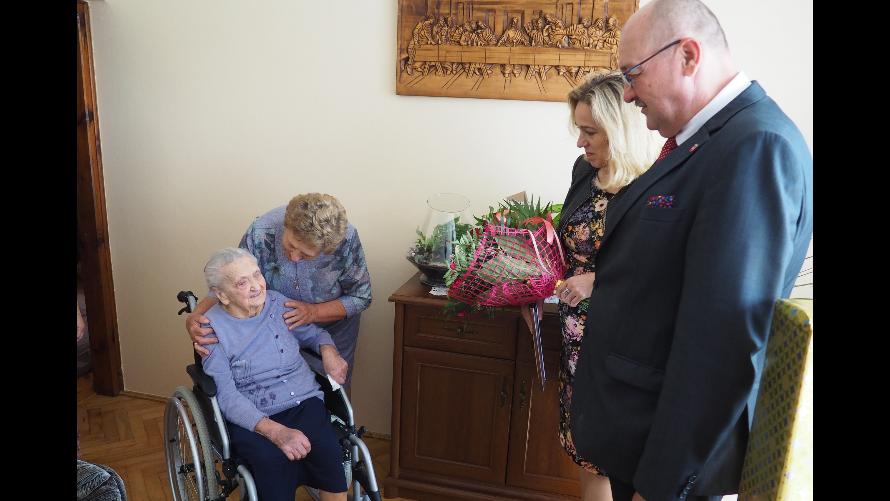 Burmistrz Urzędowa Paweł Dąbrowski wraz z kierownik Urzędu Stanu Cywilnego w Urzędowie Beata Wnuk, która trzyma kwiaty wraz z jubilatką Genowefą Węcławską, która siedzi na wózku inwalidzkim.